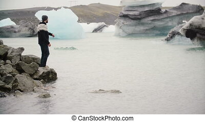 Young handsome man standing on the shore in Jokulsalon ice lagoon and looking on glaciers in Iceland.