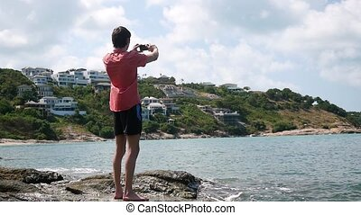 Young handsome man takes a photo with his smart phone at the rocky beach in cloudy day. Koh Samui, Thailand. slow motion.