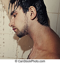 Young handsome man takes a shower closeup - Portrait of a ...