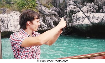 Young handsome man takes photo with phone in boat travel against rocky island in azure bay. slow motion.