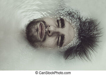 Young handsome man taking a bath