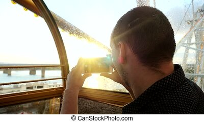 Young handsome man taking picture in a ferris wheel during beautiful sunset and sun flare effects. 3840x2160. 4k