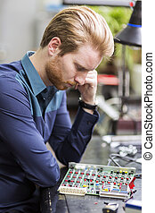 Young handsome man thinking while soldering a circuit board