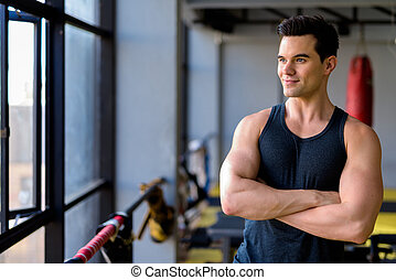 Young handsome man thinking with arms crossed at the gym