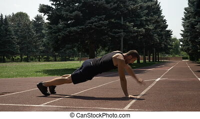 Young handsome man training on running track in the park