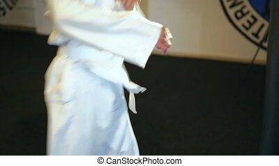 Young handsome man training taekwondo movements in the gym