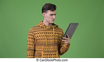 Young handsome man using digital tablet and getting bad news