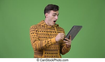Young handsome man using digital tablet and getting good news