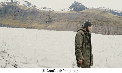 Young handsome man walking on the shore alone. Tourist exploring the Vatnajokull ice lagoon in Iceland.