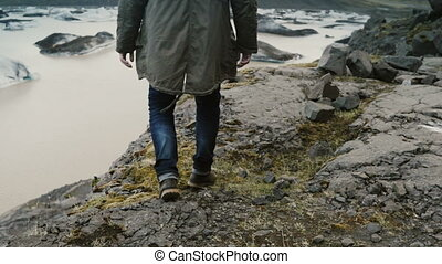Young handsome man walking through the rocks in the mountain near the Vatnajokull ice lagoon in Iceland.