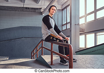Young handsome man wearing shirt and hat holding his board while sitting on a grind rail in skatepark indoors