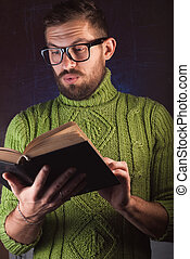 Young handsome man with a beard in green knitted sweater reading book.