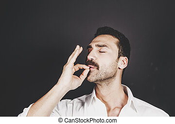 Young handsome man with beard and mustache kissing fingers, hand gesture for perfection