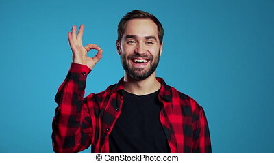 Young handsome man with beard making OK sign over blue background and smiles to camera