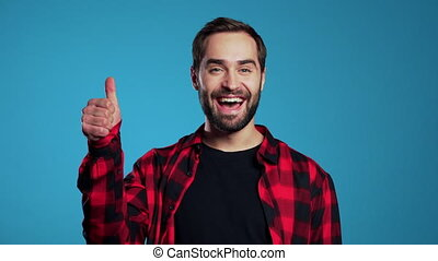 Young handsome man with beard making thumbs up sign over blue background and smiles to camera.