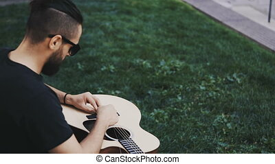Young handsome man with beard sitting on the grass in park and changing strings, restrung the guitar outside.