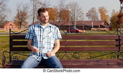 Young handsome man with bristles is sitting on a bench in...