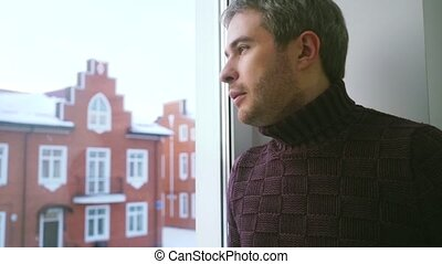 Young handsome man with grey hair looking through the window...
