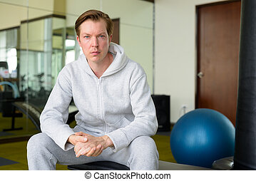 Young handsome man with hoodie sitting at the gym