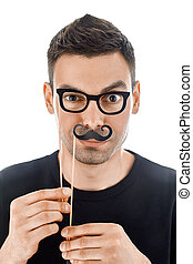 Young handsome man with paper moustaches and glasses making...