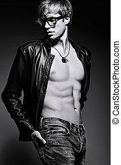 Young handsome muscled fit male model man posing in studio showing his abdominal muscles