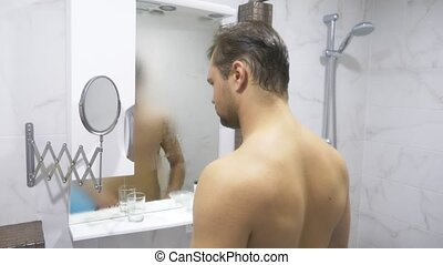 young handsome muscular man after shower in the bathroom. He...