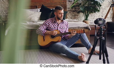 Young handsome musician popular blogger is recording video...
