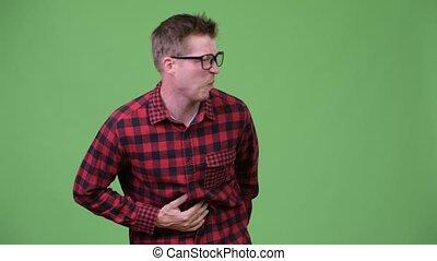 Young handsome nerd man having stomach ache - Studio shot of...