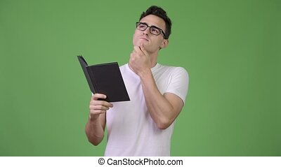 Young handsome nerd man thinking while reading book - Studio...