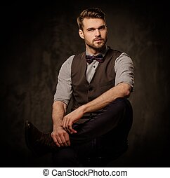 Young handsome old-fashioned  man with beard posing on dark background.