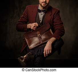 Young handsome old-fashioned man with briefcase posing on dark background.