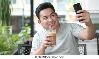 Young handsome overweight Asian man relaxing at the coffee...
