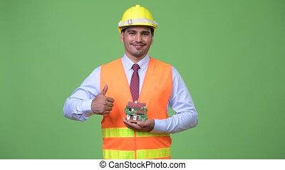 Young handsome Persian man construction worker holding house...