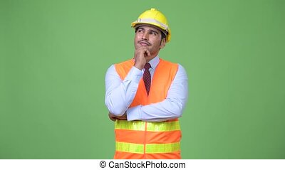 Young handsome Persian man construction worker thinking