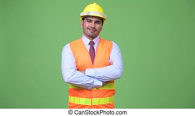 Young handsome Persian man construction worker with arms crossed