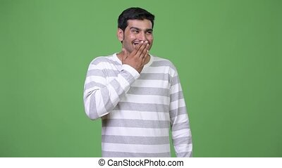 Young handsome Persian man covering mouth while looking...