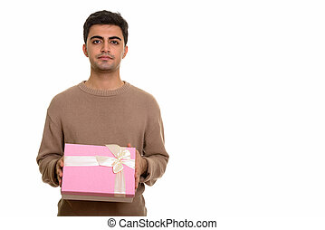 Young handsome Persian man holding gift box ready for Valentine'