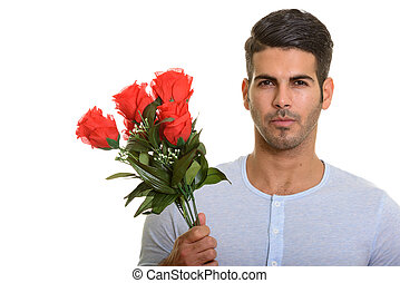 Young handsome Persian man holding red roses ready for Valentine