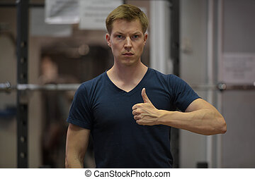 Young handsome Scandinavian man giving thumbs up at the gym