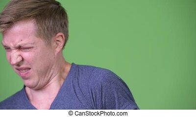 Young handsome Scandinavian man looking disgusted - Studio...