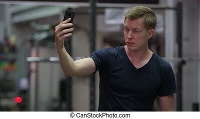 Young handsome Scandinavian man taking selfie at the gym -...