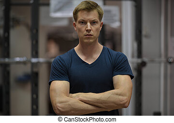 Young handsome Scandinavian man with arms crossed at the gym
