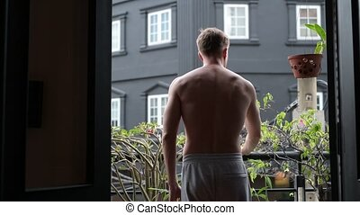 Shirtless Man Opening Door And Walking Outdoors In Balcony
