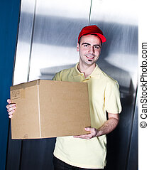 Young  handsome smiling delivery man with box