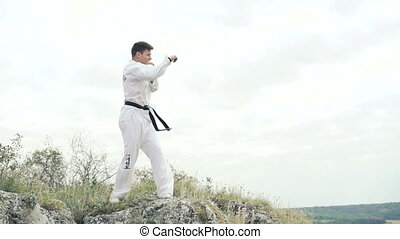 Young handsome sportsman exercising on the rock