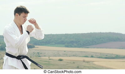 Young handsome sportsman exercising on the rock on landscape background