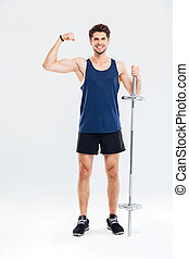 Young handsome sportsman holding barbell and showing biceps