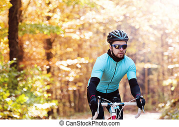 Young handsome sportsman riding his bicycle outside in sunny...