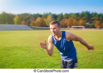 Young handsome sportsman running outdoors.