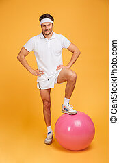 Young handsome sportsman with fitness ball holding hands on hips